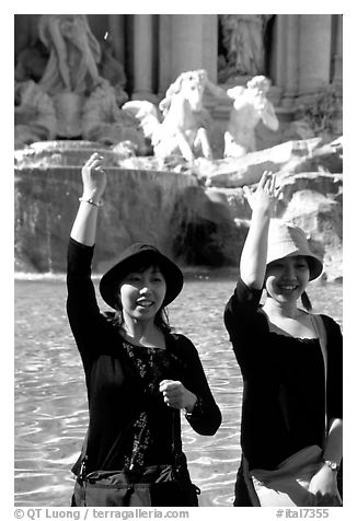 Asian tourists toss a coin over their shoulder into the Trevi Fountain. Rome, Lazio, Italy (black and white)