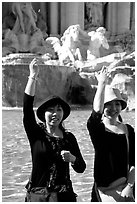 Asian tourists toss a coin over their shoulder into the Trevi Fountain. Rome, Lazio, Italy ( black and white)