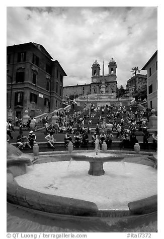 Fontana della Barcaccia and Spanish Steps covered with tourists sitting. Rome, Lazio, Italy (black and white)