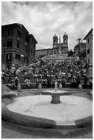 Fontana della Barcaccia and Spanish Steps covered with tourists sitting. Rome, Lazio, Italy ( black and white)