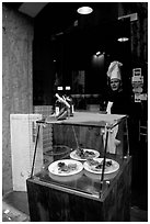 Chef at restaurant doorway with appetizers shown in glass case. Naples, Campania, Italy (black and white)