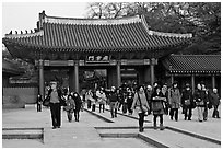 People walking down gate, Changdeok Palace. Seoul, South Korea (black and white)