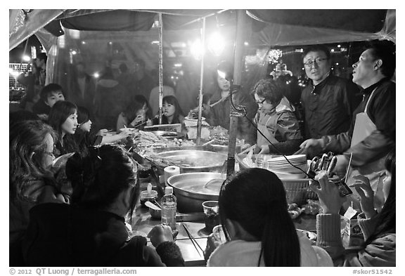 People eating noodles in a tent at night. Seoul, South Korea