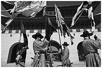 Guards carrying flags in front of main gate, Gyeongbokgung. Seoul, South Korea (black and white)