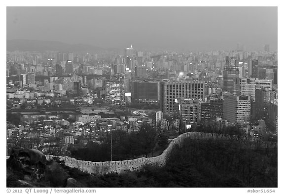 Old fortress wall and high-rises at dusk. Seoul, South Korea (black and white)