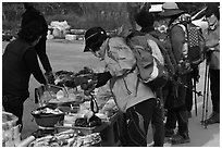 Hikers check out stand selling natural products. South Korea (black and white)