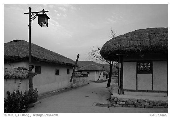 Alley bordered by straw roofed houses. Hahoe Folk Village, South Korea (black and white)