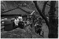 Hikers drinking from foundtain at Sangseonam hermitage, Namsan Mountain. Gyeongju, South Korea ( black and white)