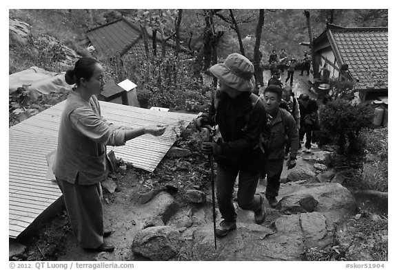 Woman giving sacred bread at Sangseonam hermitage, Namsan Mountain. Gyeongju, South Korea (black and white)
