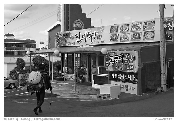 Haeneyo woman walking towards seafood restaurant. Jeju Island, South Korea (black and white)