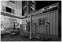 Public exercise equipment and buildings at night, Seogwipo. Jeju Island, South Korea ( black and white)