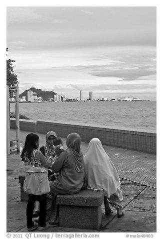 Women on waterfront. George Town, Penang, Malaysia (black and white)