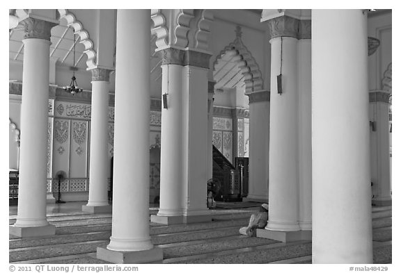 Man in prayer inside Masjid Kapitan Keling mosque. George Town, Penang, Malaysia (black and white)