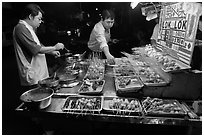 Men arranging skewers on hawker stall. George Town, Penang, Malaysia ( black and white)