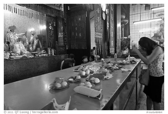 Woman Worshiping inside Chinese temple. George Town, Penang, Malaysia (black and white)