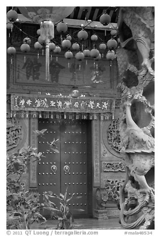 Red paper lanters, door, and stone carved wall, Hainan Temple. George Town, Penang, Malaysia