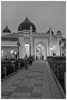 Men walking out of Masjid Kapitan Keling at dawn. George Town, Penang, Malaysia (black and white)