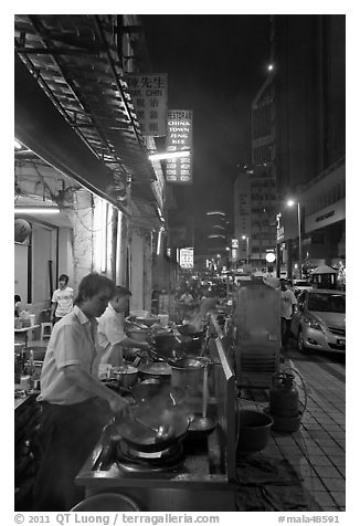 Cooks preparing food on Chinatown street at night. Kuala Lumpur, Malaysia (black and white)