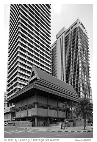 Wooden traditional building at the base of high-rises. Kuala Lumpur, Malaysia (black and white)