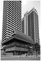 Wooden traditional building at the base of high-rises. Kuala Lumpur, Malaysia ( black and white)