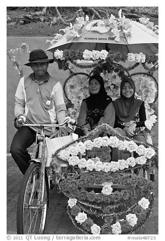 Rider and two women passengers, bicycle rickshaw. Malacca City, Malaysia (black and white)
