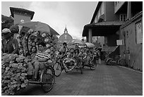 Trishaws leaving Town Square and Stadthuys. Malacca City, Malaysia (black and white)