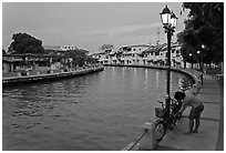 Woman locking bicyle on quay of Melaka River. Malacca City, Malaysia (black and white)