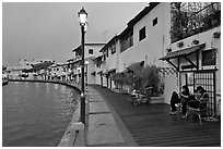Women relaxing in front of riverside house, dusk. Malacca City, Malaysia (black and white)