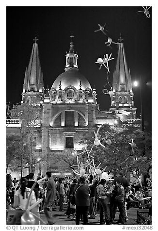 Children play with inflated balloons behind the Cathedral by night. Guadalajara, Jalisco, Mexico (black and white)