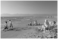 Mothers sitting on beach chairs watching children play in sand, Nuevo Vallarta, Nayarit. Jalisco, Mexico ( black and white)