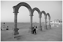 Boy standing by the Malecon arches at dusk, Puerto Vallarta, Jalisco. Jalisco, Mexico (black and white)