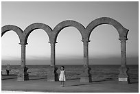 Girl standing by the Malecon arches at sunset, Puerto Vallarta, Jalisco. Jalisco, Mexico ( black and white)