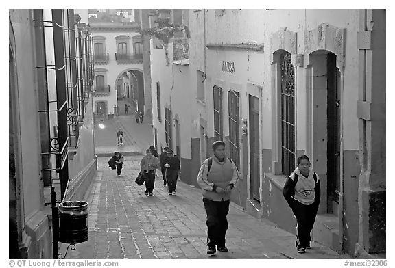 Children heading to school up a narrow cajaon, dawn. Zacatecas, Mexico (black and white)