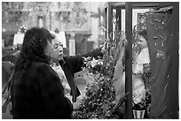 Women placing flowers in front of a Saint figure. Zacatecas, Mexico (black and white)