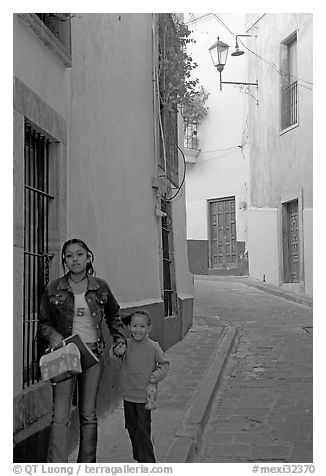Woman and child walking in a narrow street. Guanajuato, Mexico (black and white)
