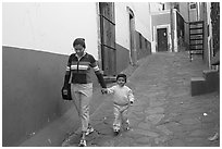 Woman and boy walking down an alleyway. Guanajuato, Mexico (black and white)
