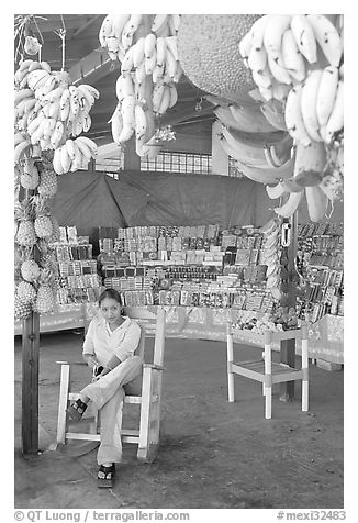 Woman sitting in a fruit stand. Mexico (black and white)