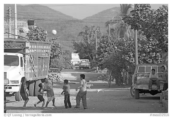 Children playing with a ball in village street. Mexico (black and white)