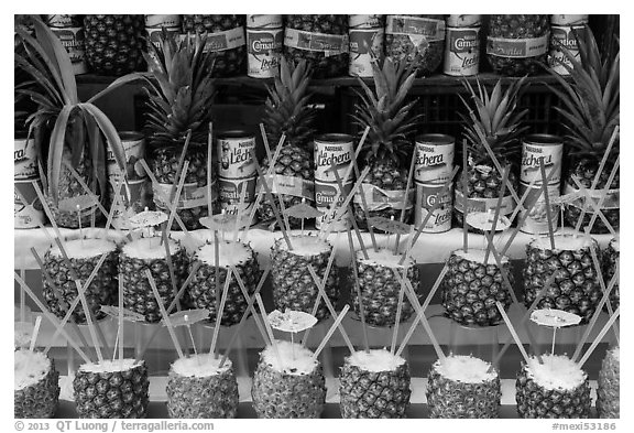 Pinacoladas prepared in pineapple shells. Baja California, Mexico (black and white)