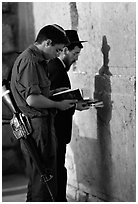 Young soldier and orthodox jew reading prayer  books at the Western Wall. Jerusalem, Israel (black and white)