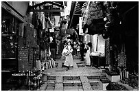 Narrow alley lined with shops. Jerusalem, Israel (black and white)