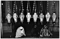 Women worshiping beneath hanging lamps inside the Church of the Holy Sepulchre. Jerusalem, Israel (black and white)