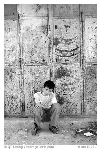 Young boy sitting in front of a closed store, Hebron. West Bank, Occupied Territories (Israel) (black and white)
