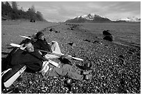 Kayakers relaxing on a beach between Rendu Inlet and Russel Island. Glacier Bay National Park, Alaska (black and white)