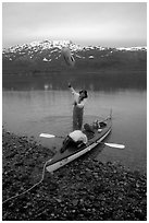 Kayaker unloading the kayak by throwing stuff sacks out. Glacier Bay National Park, Alaska (black and white)
