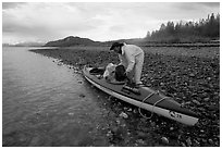 Kayaker unloading gear from a double kayak. Glacier Bay National Park, Alaska (black and white)