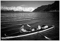 Kayaker sitting at a rear of a double kayak with the Fairweather range in the background. Glacier Bay National Park, Alaska (black and white)