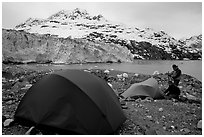 Campers set-up a tent in front of Lamplugh Glacier. Glacier Bay National Park, Alaska (black and white)