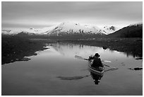 Kayaker paddles in  a shallow tidal channel into Scidmore Bay. Glacier Bay National Park, Alaska (black and white)