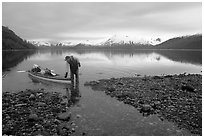 Kayaker standing in Scidmore Bay next to a shallow tidal channel. Glacier Bay National Park, Alaska (black and white)